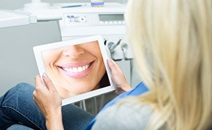 Woman looking at smile photo on tablet computer