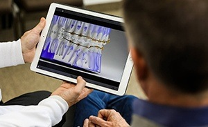 Dentist showing patient fastbraces system on computer