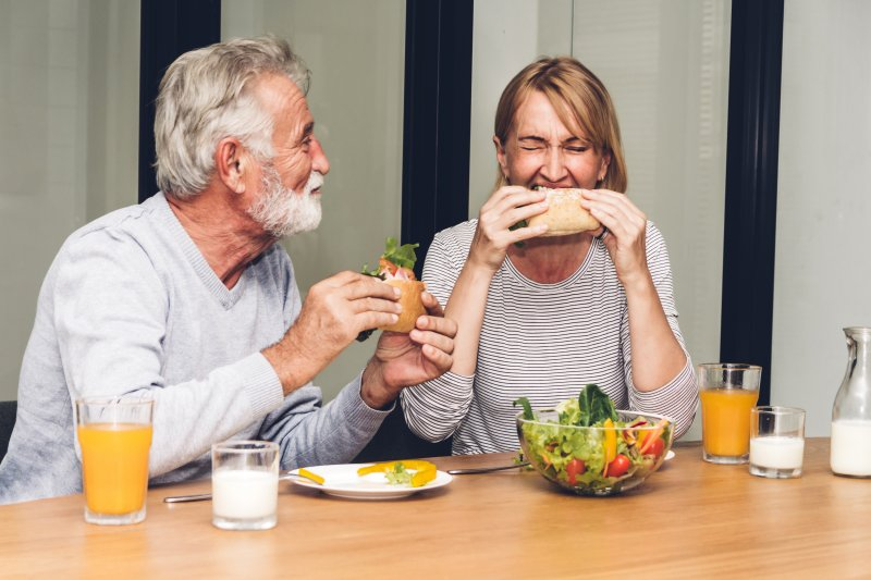 older couple eating food together in the kitchen