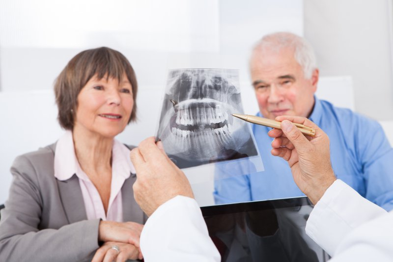 Older couple learning about the basics of dental implants